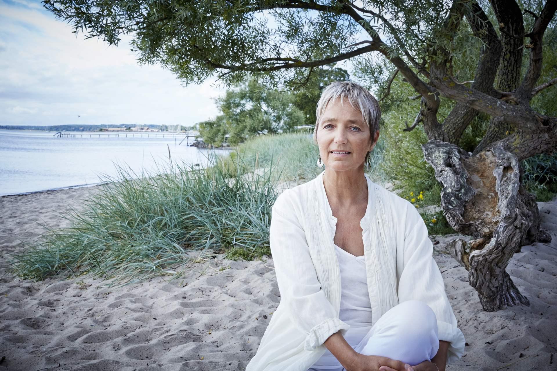 Eva sidder på en strand i naturen